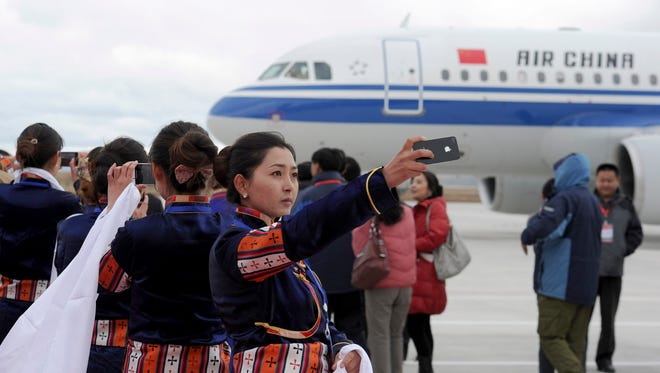A Tibetan woman takes photos on the runway of Daocheng Yading Airport on Sept. 16, 2013.
