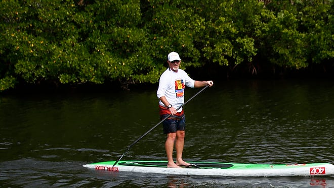 Mark Payne of Estero passes on a paddleboard Saturday, Dec. 5, 2015, at Lovers Key State Park in Fort Myers.