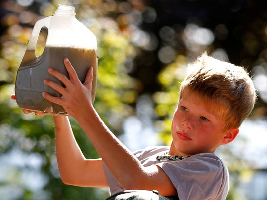 Samuel Hudspeth, 8, holds the juice he crushed from chardonnay grapes during a children's event at the 24th Annual Grape Stomp Championship and Harvest Celebration at Willamette Valley Vineyards on Sunday, Sept. 21, 2014, in Salem, Ore.