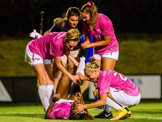 FSU players swarm Tillman after her game winning goal.
