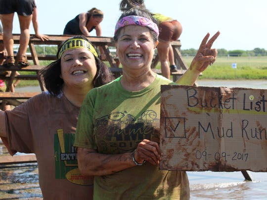 Mudslinger Fun Run participants Wanda Cleveland, who was stationed at Dyess Air Force Base, left, and Teena Beshk carried their sign with them on the 5K course, then celebrated finishing the seventh annual event last year.