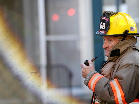A firefighter smokes a pipe at the scene of a two-alarm fire on the 500 block of West King Street Wednesday, December 5, 2012.  DAILY RECORD/SUNDAY NEWS - KATE PENN