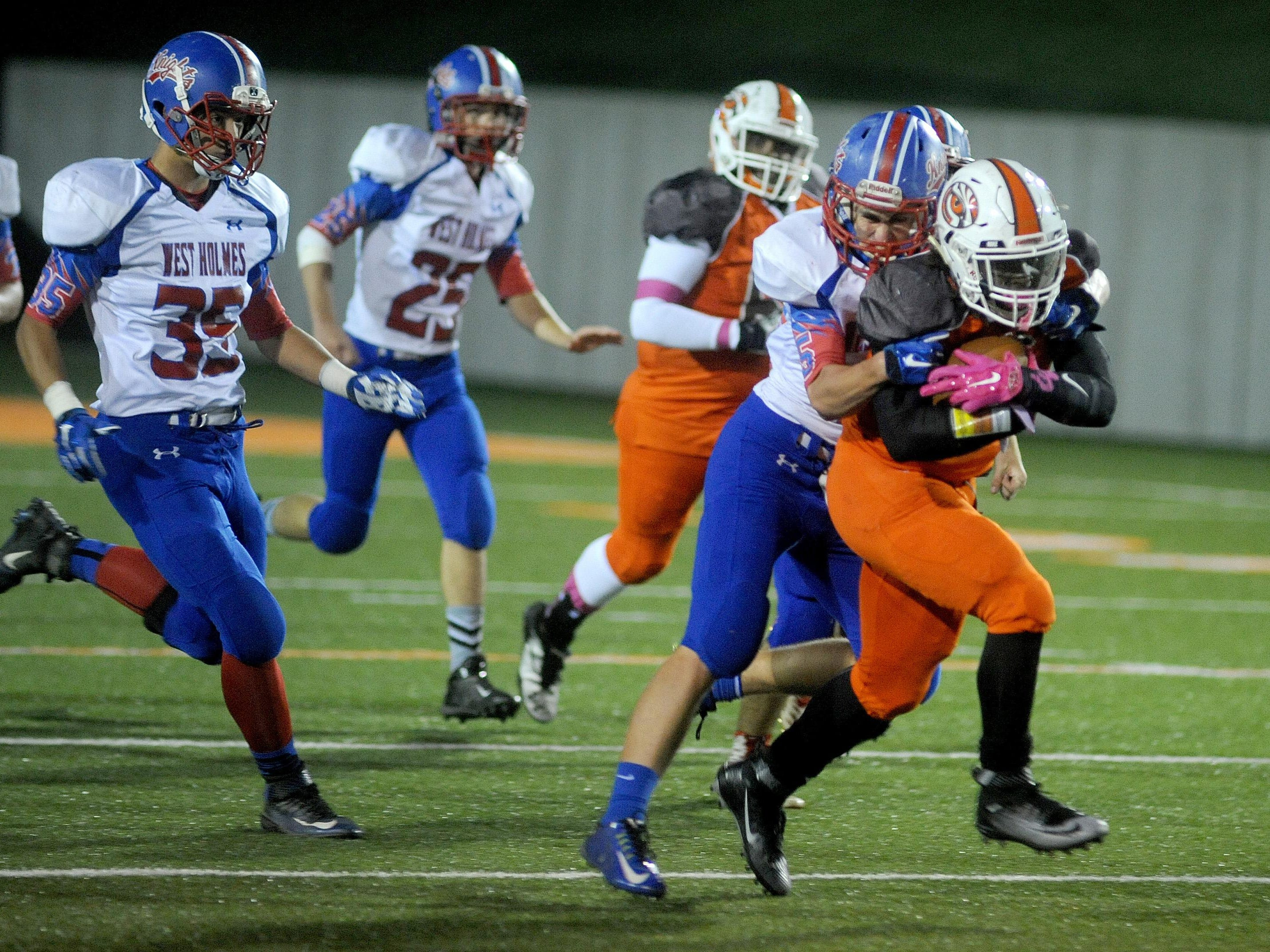Connor Roach of West Holmes clutches on to Mansfield Senior's Tyquan Vickers after he picked up big yards on a long run Friday night at Arlin Field.
