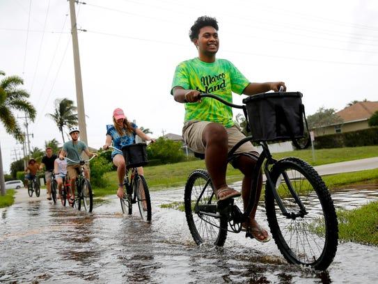 The Kyle family bikes through the flooded sidewalks