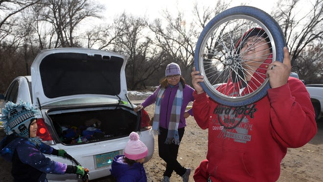 Derrell Cohoe, front, checks his handiwork after replacing a tire at the start of a family bike trip on Saturday at Berg Park in Farmington.