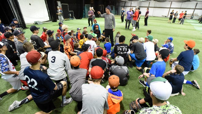 Albuquerque Baseball Academy's Ryan Brewer talks with a group of kids at the Grinders for Grace camp Jan. 9, 2016, at the Strike Zone training facility in Farmington.