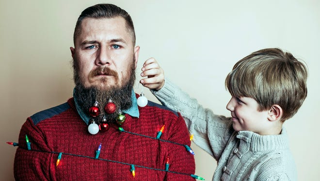 Little boy having fun decorating his dad as a Christmas tree.