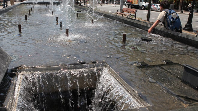 A boy dips his hand in the fountain at the Renaissance Plaza as he runs by in downtown White Plains on June 8, 2011.