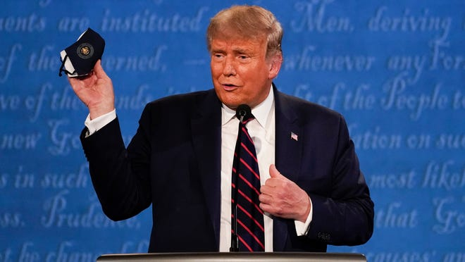 In this Sept. 29, 2020, file photo, President Donald Trump holds up his face mask during the first presidential debate at Case Western University and Cleveland Clinic, in Cleveland, Ohio. President Trump and first lady Melania Trump have tested positive for the coronavirus, the president tweeted early Friday.