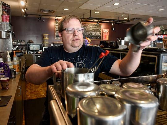 Alan Scherr, co-owner of Central Cafe coffee shop, creates a coffee drink for a customer on April 25, 2018, in St. Cloud. The coffee shop will have its last day of business March 31.
