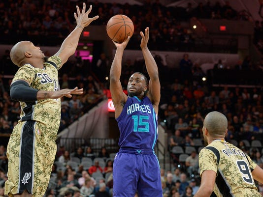 Charlotte Hornets guard Kemba Walker (15) shoots against San Antonio Spurs forward David West (30) and Spurs guard Tony Parker, of France, during the first half of an NBA basketball game, Saturday, Nov. 7, 2015, in San Antonio. (AP Photo/Darren Abate)