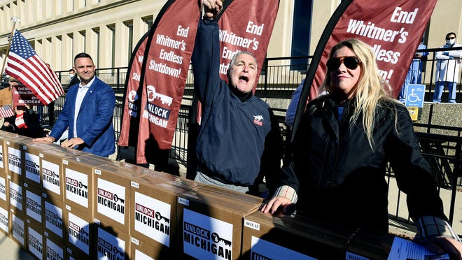 Unlock Michigan Co-Chairs Garrett Soldano, Ron Armstrong and Meshawn Maddock, left to right, speak to supporters in Lansing Friday morning. Boxes filled with a reported 539,384 petition signatures were delivered by Unlock Michigan to the Michigan Department of State Bureau of Elections in Lansing Friday, October 2, 2020. The group is seeking to revoke Governor Gretchen Whitmer's ability to govern by emergency decree.