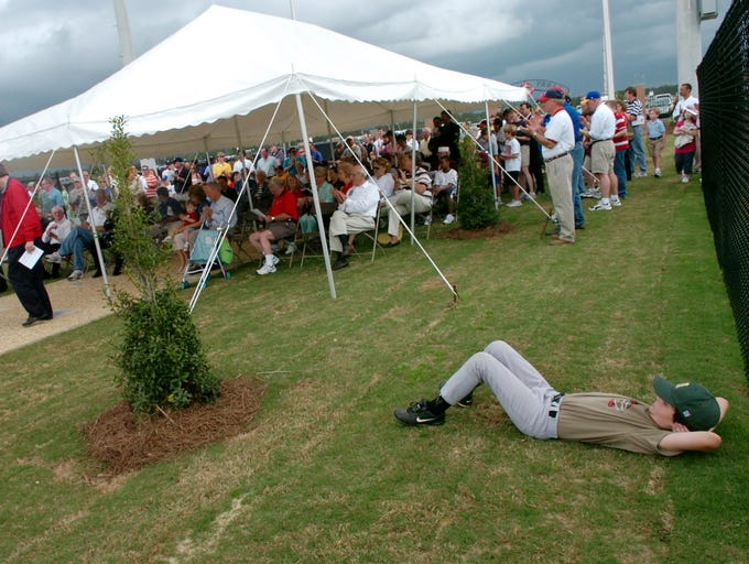 Patrick McGee lays in the grass during the opening day ceremony of the Larry Doleac Youth Baseball Complex.