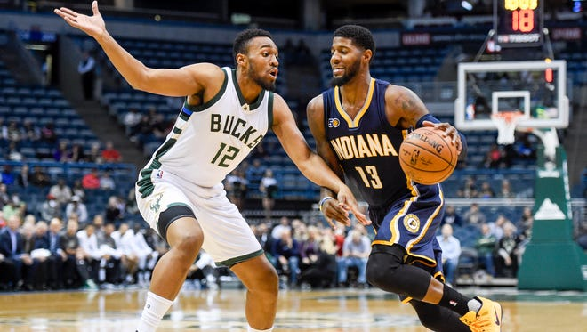 Indiana Pacers forward Paul George (13) drives for the basket against Milwaukee Bucks forward Jabari Parker (12) in the first quarter at BMO Harris Bradley Center.