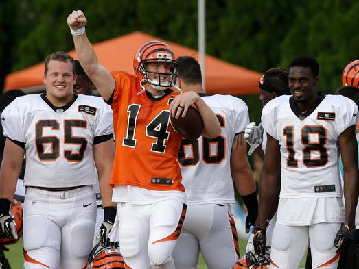 Cincinnati Bengals quarterback Andy Dalton (14) cheers from the sidelines with Clint Boling (65) and A.J. Green (18) while the kickoff squad practices.