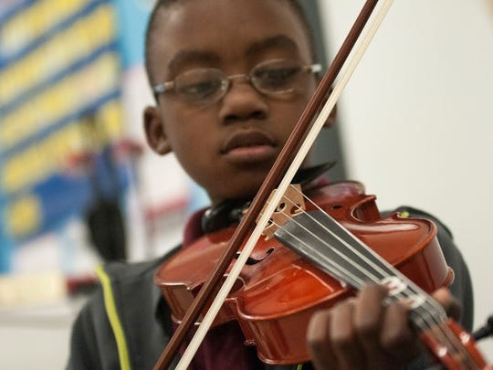 Joshua Stewart of Capitol Elementary practices with a viola during a Kids' Orchestra lesson at Belfair Montessori Magnet.