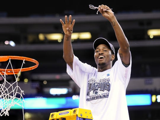 MSU's Kalin Lucas holds up four fingers for the Final Four as he cuts down the nets after MSU beat Louisville 64-52 in the NCAA tournament Sunday March 29 in Indianapolis. The victory sent the Spartans back to their home state to play on the biggest stage in Detroit's Ford Field.