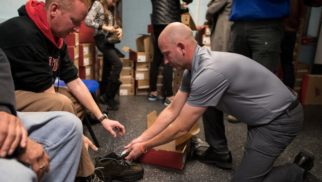 "Volunteer Aaron Drury, right, helps size Chris Campbell, a resident in Louisville's Healing Place for four months, into a new pair of Red Wings at the Healing Place recovery facility in downtown Louisville. ""What I'm seeing here is that you can always give charity to someone else. You don't always have to receive from someone,"" Campbell said. ""That inspires me to try to give even more."" The Hearts to Soles event is in its 11th year in Louisville and this year 120-130 pairs of Red Wing boots were donated to those in need. Nov. 22, 2017"