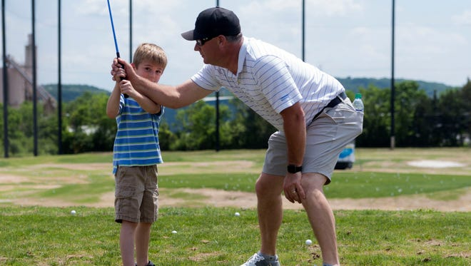 Ryan Ott of golf pro and Tennessee National teaches Tucker Balanetsky golf tips during the Food City Kid's Clinic at Fairways and Greens. on Sunday, May 6, 2018. The event kicks off a week of festivities for the Knoxville Open.