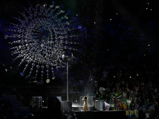 Marlene de Castro performs under the cauldron with the Olympic flame gone during the closing ceremony in the Maracana stadium at the 2016 Summer Olympics in Rio de Janeiro, Brazil, Sunday, Aug. 21, 2016. (AP Photo/Natacha Pisarenko)
