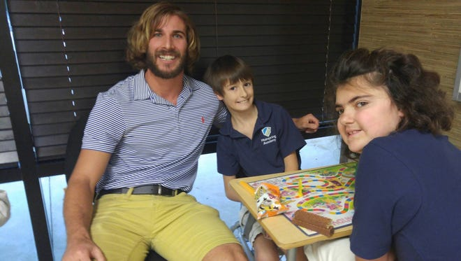 Teacher Chris Ulmer sits with two of his students in his classroom in Jacksonville, Florida.