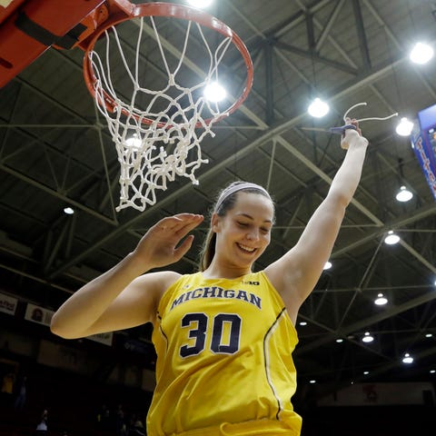 Michigan center Hallie Thome cuts the net after...