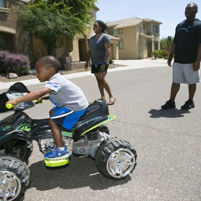 Aiden Corley, 3, drives a toy ATV as his parents, Air