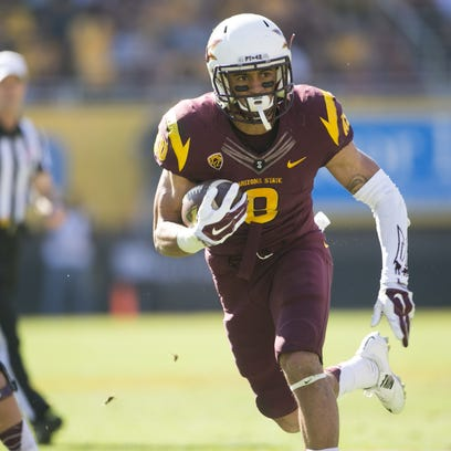 ASU running back D.J. Foster carries the ball for a