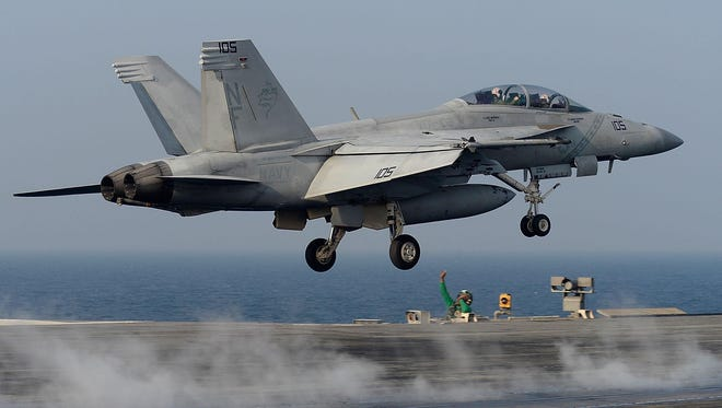 U.S. Navy crew members guide an F/A-18 Super Hornet fighter takes off from the deck of USS Aircraft Carrier Ronald Reagan on October 14, 2016 in Weat sea, South Korea.