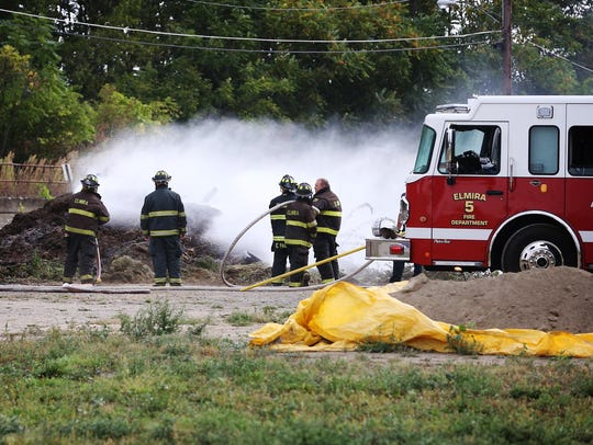 Elmira firefighters spray water in a smoking mulch