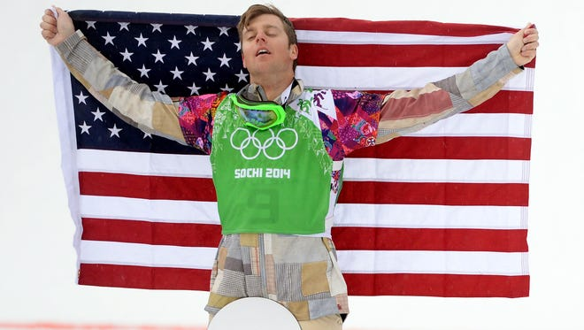 Alex Deibold (USA) holds up the United States flag during the flower ceremony after the big final run of the men's snowboard cross finals during the Sochi 2014 Olympic Winter Games at Rosa Khutor Extreme Park.