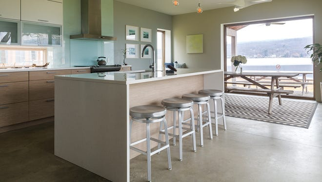 The couple located the eat-in kitchen in the back of the house, surrounded by two walls of sliding windows leading out to the lake, because they knew it would be an ideal gathering spot while entertaining.