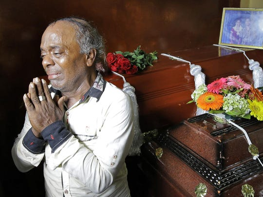 Baby Joseph Gomes prays standing next to coffins of his family members killed in the Easter Sunday bombings in Colombo, Sri Lanka, Tuesday, April 23, 2019. Gomes lost five members of his family.