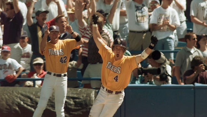 First base coach Daniel Tomlin (42) celebrates as Warren Morris rounds first base after hitting the home run that gave LSU the 1996 national championship.