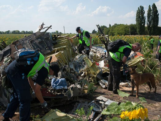 Australian, Malaysian and Dutch investigators examine pieces of the downed Malaysia Airlines Flight 17 near Rossipne, Ukraine on Aug. 5. The jet crashed on July 17, killing all 298 people on board.