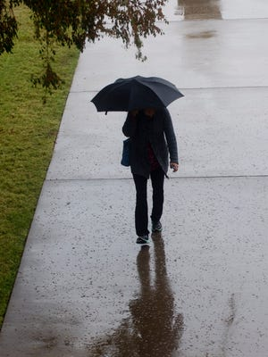 A woman walks toward the McMurry University library on a rainy Thursday.