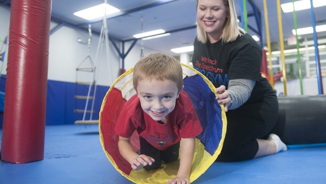 Julie LaRochelle, who owns We Rock The Spectrum Kid's Gym For ALL Kids - Mount Laurel with her husband, Charlie, watches as her son Shane, 4, plays in the gym. The indoor play space is designed to accommodate families affected by autism and other sensory processing disorders.