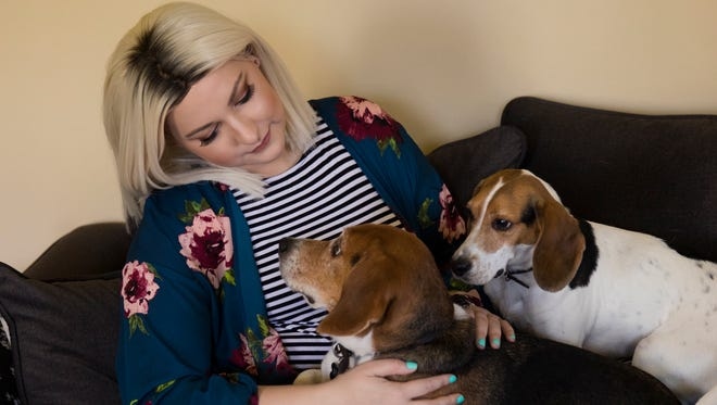 """Charli Ray, 26, currently fighting breast cancer, sits in her living room with 8-year-old beagles Hank and Albus Friday, April 20, 2018 in Louisville, Kentucky. """"They are my babies,"""" Ray says her dogs are her support, along with her family and friends."""