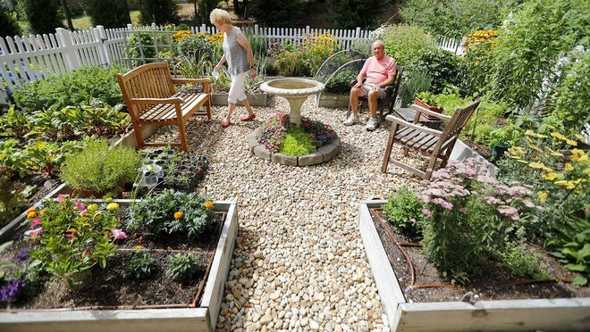 Mary and Jim Kelly, of Duxbury, relax in a garden area behind their home with a stone bird bath in the center.