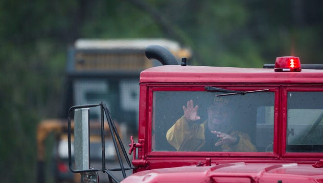 Fire crews drive out of the brush fire area on Frangipani Avenue on Wednesday, May 24, 2017 in Golden Gate Estates. Currently, the 60 acre fire is 80 percent contained.