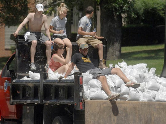 Volunteers ride along with sandbags to be used to help keep flood waters at bay in Iowa City on Saturday, June 14, 2008.