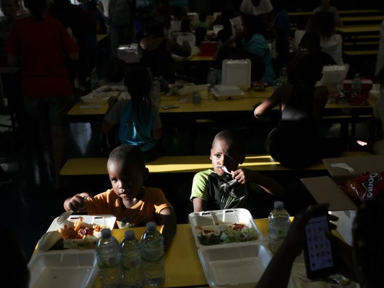 Lamar Harris orange,3, and his brother, Elijah Towns,5, enjoy a meal at Franklin Park Elementary School in Fort Myers, Florida on Monday, 9/18/2017. The food was provided by the Red Cross, cooked by the Southern Baptist Convention Disaster Relief Team and brought/served at the school by the Salvation Army alongside Franklin Park Elementary and other school district teachers and staff. Harris and Towns' family lost hundreds of dollars in food after losing power for eight days after Hurricane Irma impacted Southwest Florida.