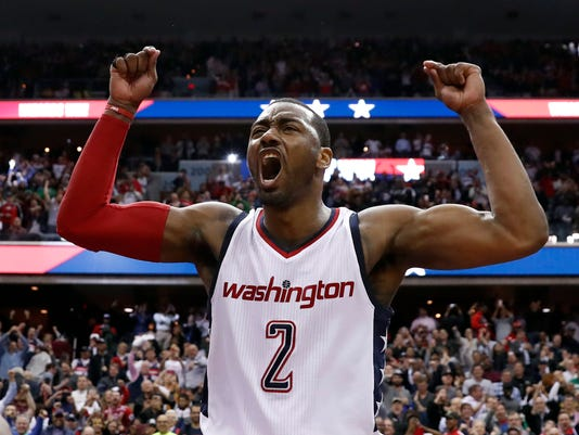 FILE - In this May 12, 2017, file photo, Washington Wizards guard John Wall celebrates as he stands on the scorer's table after Game 6 against the Boston Celtics in an NBA basketball second-round playoff series in Washington. A person familiar with the deal says that Wall has agreed to a $170 million, four-year contract extension with the Wizards that will start with the 2019 season. (AP Photo/Alex Brandon, File)