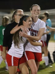 North Fort Myers' Kendal Davis hugs teammate Michele Cohen as they leave the field after their win. District 3A-13 girls soccer championship game between Mariner and North Fort Myers. Fort Myers won 1-0.