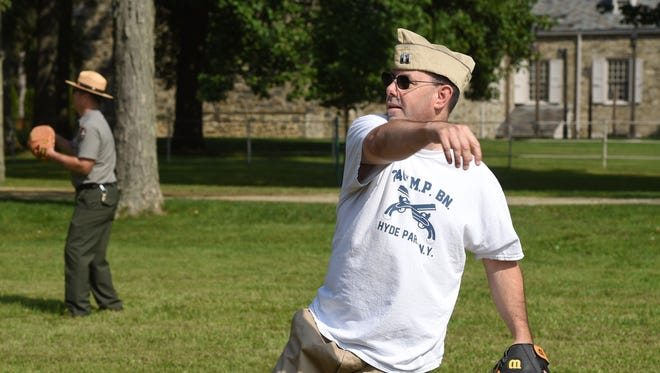 Michael Twardy, a National Park Service ranger at the Home of Franklin D. Roosevelt National Historic Site, has a catch during Organizational Day on the grounds in Hyde Park. The event is a recreation by the Living History group 240th Military Police Battalion, with Twardy acting as captain.
