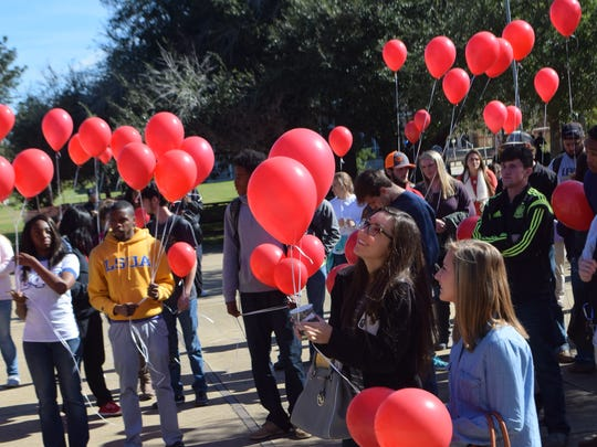 "LSU of Alexandria students, faculty and staff gather in the campus quad Tuesday with red balloons. The LSUA Student Government Association held  the ""LSUA Release for Peace""  to honor those around the world affected by terror and natural disasters."