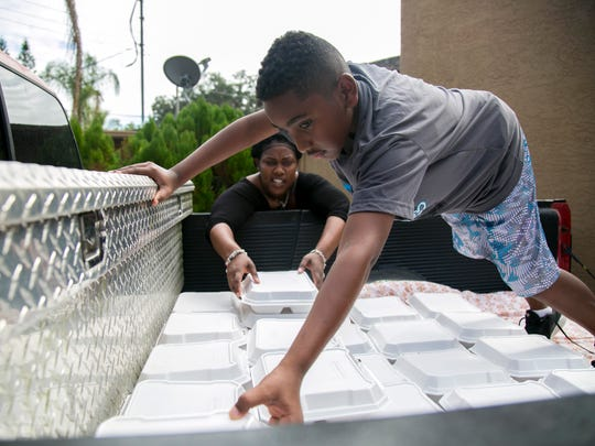 Ahmir Miller, 10, and his mother Niki Ferguson load about 90 meals into a pickup truck for delivery on Saturday, December 17, 2016, in Fort Myers.
