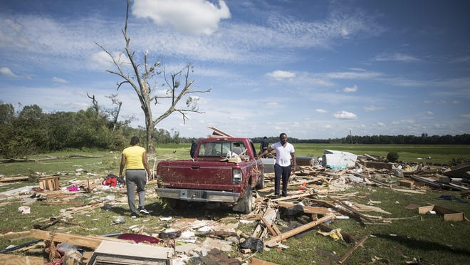 Relatives of a woman who was injured when a suspected tornado ripped through the area southeast of Windsor sort through the rubble on Tuesday.