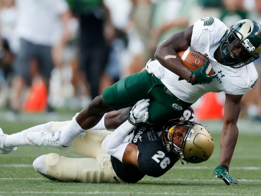 Colorado State wide receiver Michael Gallup, top, is dragged down after pulling in a pass by Colorado defensive back Isaiah Oliver in the first half of an NCAA college football game Friday, Sept. 1, 2017, in Denver. (AP Photo/David Zalubowski)
