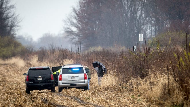 Sheriff deputies and the county coroner look over a remote area between Yorktown and Daleville on Nov. 28, 2016,  where human remains had been found. Efforts to identify the remains are ongoing.